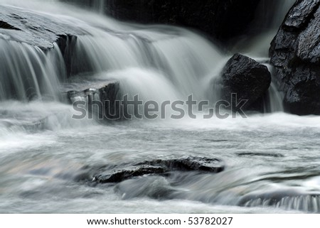 Silky smooth small waterfall with flowing water over rocks. - stock photo