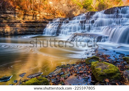 Silky water cascades over limestone rock at Burgess Falls State Park in Tennessee. - stock photo