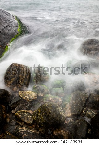 Silky waves covering rocks by the shore