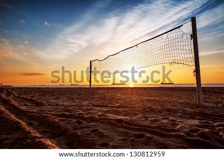 Sillhouette of a volleyball net and sunrise on the beach - stock photo