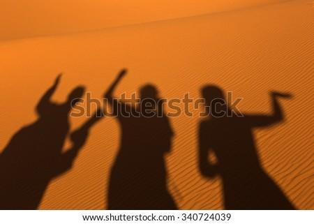 Sillhouette of people in sands on desert Sahara - stock photo