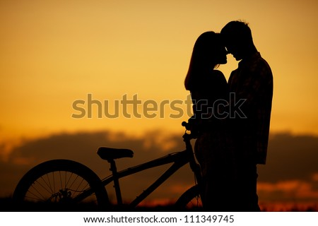 sillhouette of sweet young couple in love standing in the field. Outdoor shot - stock photo
