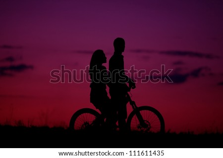sillhouette of sweet young couple in love standing in the field. sunset (dawn). Outdoor shot - stock photo