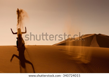 Sillhouette of woman playing and throwing with sands in Desert Sahara, creating berber sign from sillhouette and shaddow, Morocco