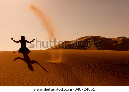 Sillhouette of woman playing and throwing with sands in Desert Sahara, creating berber sign from sillhouette and shaddow, Morocco - stock photo