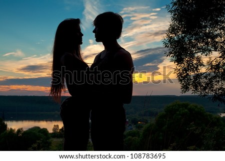 sillhouette of young loving couple at sunset near lake - stock photo