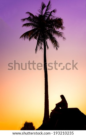 Sillouette of coconut tree and young muslim woman during sunrise - stock photo