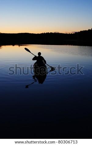 Sillouette of man kayaking on lake - stock photo