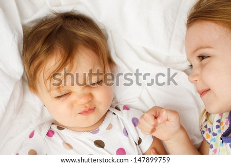 Silly baby in sheets with big sister - stock photo