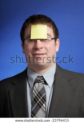 Silly businessman with yellow sticky note on forehead - stock photo