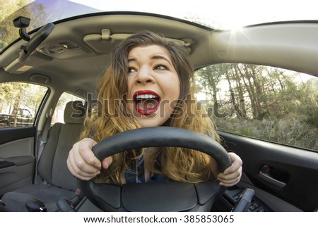 Silly girl gets into car crash and makes ridiculous face - stock photo