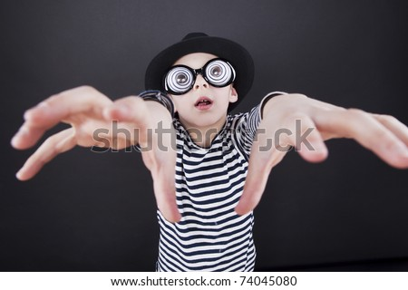 Silly little boy in black hat and striped vest with play eyeball glasses - stock photo