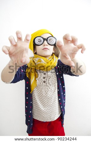 Silly little girl ten years old in yellow knitting  hat  with play eyeball glasses. I'm coming for you - stock photo