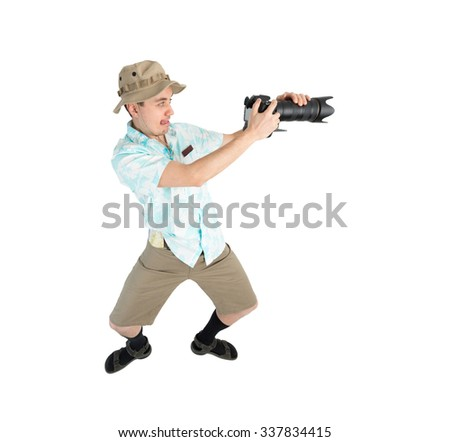 Silly man tourist in blue shirt, brown shorts and hat holding big dslr camera and shooting. Traveler concentrating and making pictures. Isolated on white background.