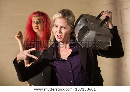 Silly mature European woman playing radio near startled teenager - stock photo