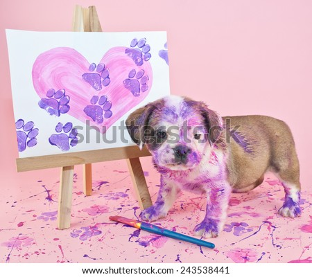 Silly puppy that made a mess painting a picture of a heart with paw prints going through it. - stock photo