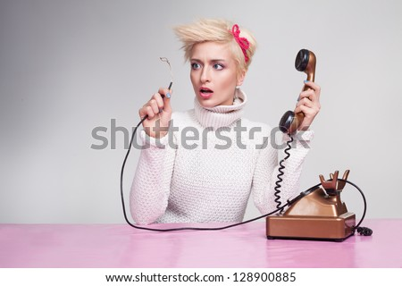 silly secretary finds out why phone not working - stock photo