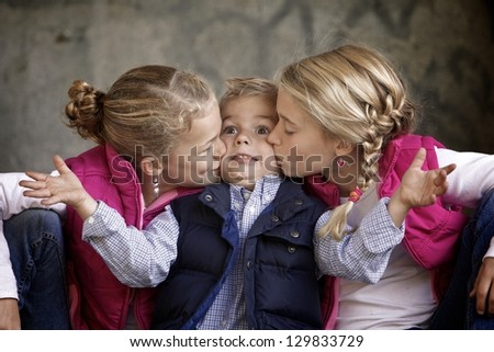 Silly siblings together with brother getting kissed - stock photo
