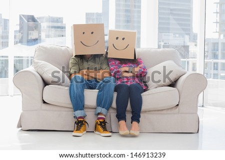 Silly workers wearing boxes on their heads with smiley faces on a couch - stock photo