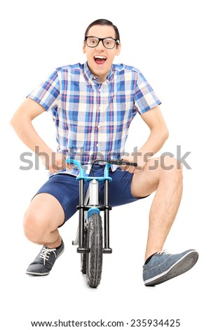 Silly young man riding a small childish bike isolated on white background - stock photo