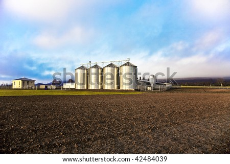 Silo in beautiful landscape with dramatically light placed in ploughed acres - stock photo