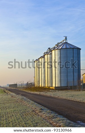 silos in the middle of a field in wintertime - stock photo