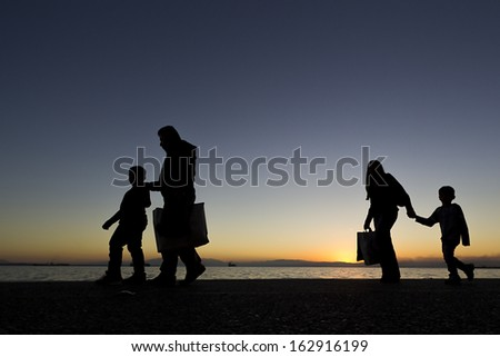 Silouetes of people walking on the sunset  - stock photo