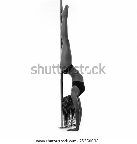 Silouette of woman performing pole dance. Studio shot, black and white image. - stock photo