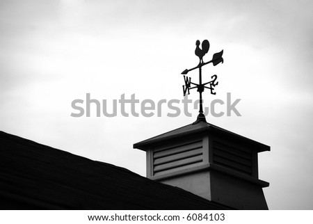 Siloutte of a wind direction at the top of a roof - stock photo
