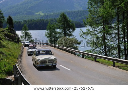 SILS, SWITZERLAND - JUNE 14: A cream-colored Volvo Amazon and other classic cars take part to the Summer Marathon classic car race on June 14, 2014 near Sils. The Volvo was built in 1951 - stock photo
