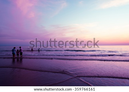 Siluate or Silhouette of people who spent time in the sea sand and beach in the purple sky at the sutset. Concept of friendly family.