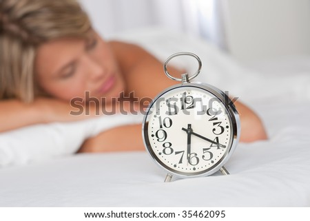 Silver alarm clock, woman in background unsharp