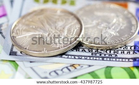 Silver American dollar coins over different bank notes background