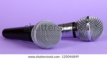 Silver and black microphones on purple background