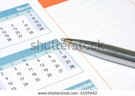 Silver and gold ballpoint pen on a calendar, with notes column.