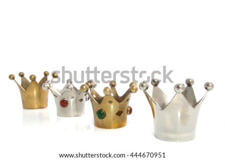 Silver and golden crowns in a row isolated over white - stock photo