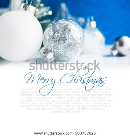 Silver and white xmas ornaments on blue bokeh background. Merry christmas card. Winter holiday theme. Happy New Year. Space for text.