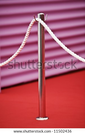 Silver barrier at a red carpet event with a pink wall in the background. - stock photo