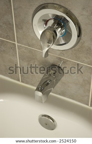 Silver bath tap and faucet against grey tile - stock photo