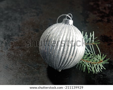 Silver bauble Christmas decoration with a ridged pattern with a twig of pine needles on a dark background with copyspace for your seasonal message - stock photo