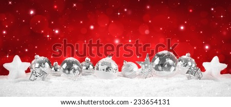 silver Baubles on snow with red sparkle background  - stock photo