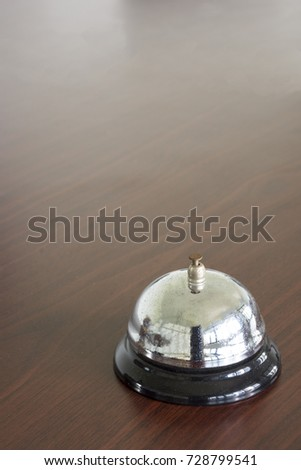 Silver bell on brown wood table