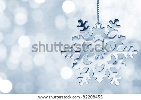 Silver blue snowflake against shimmering background - stock photo