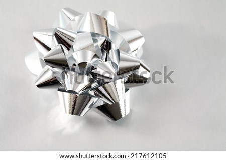 Silver bow on matching wrapping paper for Christmas and other gift giving occasions.  - stock photo