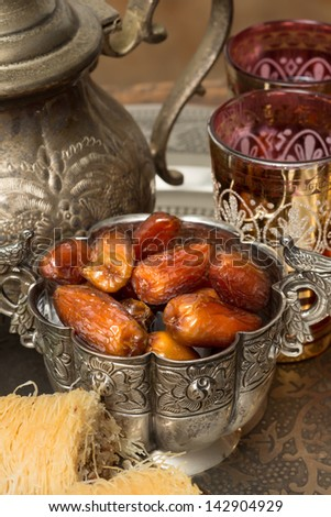 Silver bowl filled with dates as traditional Ramadan treat  - stock photo