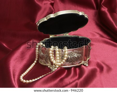 Silver box with string of pearls over purple fabric - stock photo