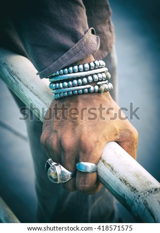 Silver bracelet and ring on a man's hand. Cross process. - stock photo