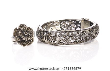 Silver bracelet and ring on white a background - stock photo