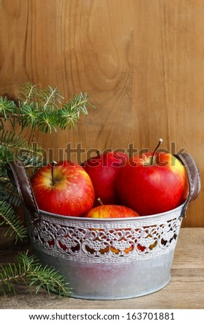 Silver bucket of red apples on wooden table. Fir branches in the background - stock photo