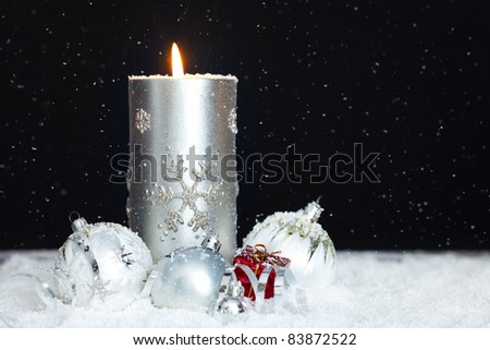 silver candle with christmas balls with snow falling and space for text - stock photo